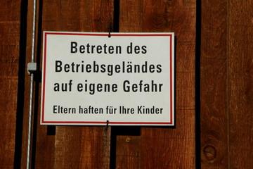 """German Sign """"Enter the premises at your own risk"""" , Schild in einem Betriebsgelände"""