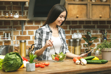 Autocollant pour porte Cuisine Young beautiful woman with tablet computer on kitchen finding recipes and tasting food. Food blogger concept