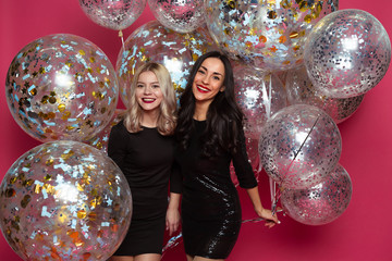 Holiday with helium balloons. Two beautiful smiling modern women in little black dresses are posing in front of the camera on a pink background with large helium balloons.