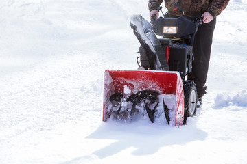 man cleans snow with a snow-removing machine