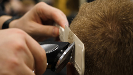 Young Man in Barber Shop Hair Care Service Concept. Man's hands doing a haircut for man at barber shop, close up