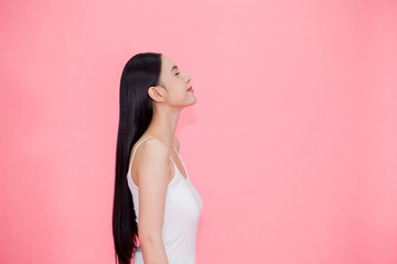 Side view of Young beautiful and calm Asian woman isolated over pink background.