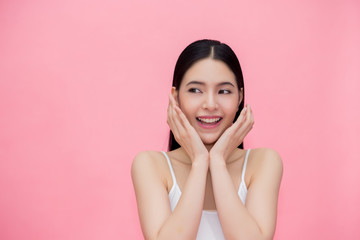 Excited and surprised smiling Asian 20s woman isolated over pink background.