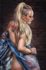 blonde girl with tattoos in sheer dress on brick wall background