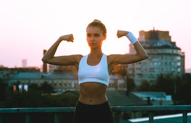Feel the power of the city. Young beautiful woman in sportswear showing her arm muscles while standing against industrial city view with sunrise