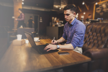 Handsome young businessman working with laptop and mobile phone