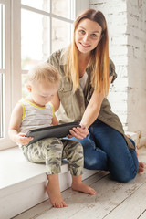 Mom and child with tablet. Young smiling mother and her son at home