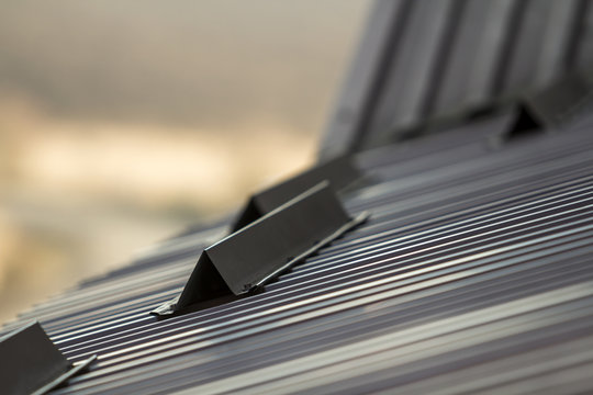 Metal roof of a house close up with snow guards safety.
