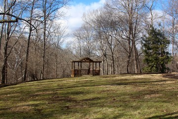 The wooden gazebo in the grass landscape on sunny day.