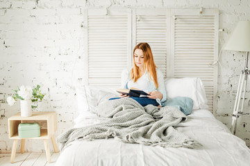 Cute Redhead Woman Reading Book at Home. Girl with Grey Woolen Blanket