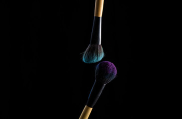 Make up brushes with powder on black background