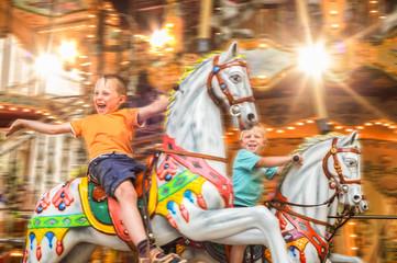 begeisterte Kinder auf einem Karussell mit Pferden