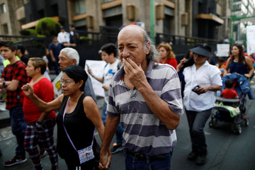 A couple takes part in a march by victims of September 19 earthquake demanding transparency in the delivery of resources for the reconstruction in Mexico City