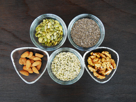 Five superfood seeds and nuts chia, almond, walnut, hemp, pumpkin in glass bowl over dark wooden table