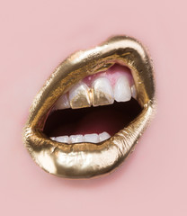 Foto op Plexiglas Fashion Lips Golden lip make up. Gold paint on lips and teeth. Open mouth and white teeth isolated on pink background. Part of rich face covered in gold. Modern make-up for women. Sensual golden luxury concept
