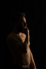 shirtless, handsome young man standing. Studio shot of light,