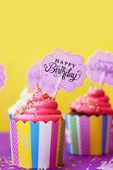 Tasty strawberry cupcake in colorful paper baking cup, with 'Happy Birthday'  topper, on yellow background. Birthday background