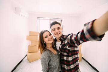 Happy attractive young couple is moving, making a selfie, cuddling and smiling while sitting among cardboard boxes in new room