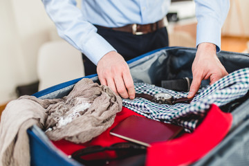 Man preparing for business travelling. Open traveler's bag with passport, clothing and accessories. Travel and vacations concept.