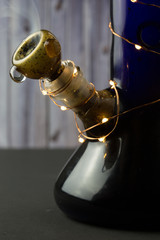 Blue bong with small lights wrapped around
