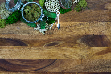 Marijuana in glass jar surrounded by moss, grinder, tool with wooden background