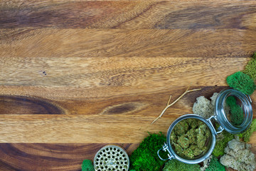 Marijuana in glass jar surrounded by moss and grinder with wooden background