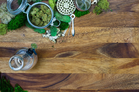 Marijuana in glass jar surrounded by moss, grinder, tool and bong with wooden background