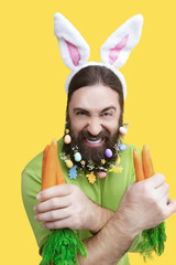 Happy Easter concept. Nice kind muscle man male with spring's flower's beard, white ears of rabbit, carrots in green t-shirt isolated on yellow background