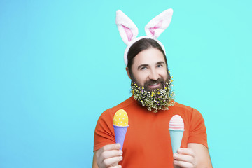 Happy Easter concept. Nice kind muscle man male with flower's beard  with white ears of rabbit and colorful easter eggs in waffle in orange t-shirt isolated on blue background