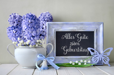 "Blue decorations and hyacinth flowers on white table, blackboard with text ""Alles gute zum geburtstag"""