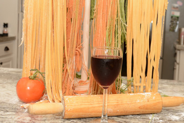 Glass of wine in front of pasta drying on wooden tree rack