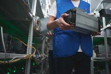Mining. A man works on a cryptocurrency farm. Holds bitcoin mining equipment in hand