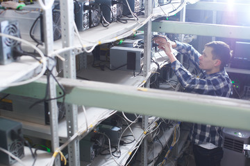 Mining. A man working on a farm for the extraction of crypto currencies. Bitcoin business