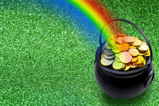 Saint Patrick's Day and Leprechaun's pot of gold coins concept with a rainbow indicating where the leprechaun hid treasure on green with copy space. St Patrick is the patron saint of Ireland