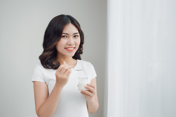 Portrait of young asian woman at home eating yogurt