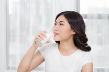Beautiful asian girl drinking a glass of milk.