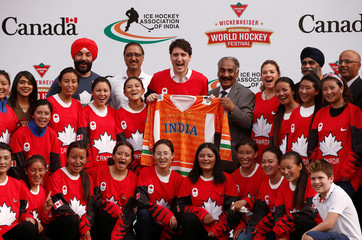 Canadian Prime Minister Justin Trudeau his wife Sophie Gregoire Trudeau and son Xavier (R-bottom) pose for a picture with India's Women Ice Hockey Team players during an event in New Delhi
