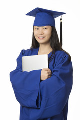 Asian woman holding computer wearing blue graduation gown isolated on white background