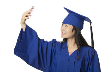 Asian woman using a smartphone to take a salfie of herself wearing a blue graduation gown