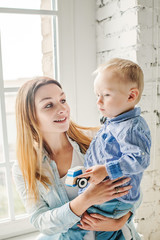 Happy Sun and her Mom Hugging at Home Lifestyle Portrait. Woman and Child Wearing Blue Denim