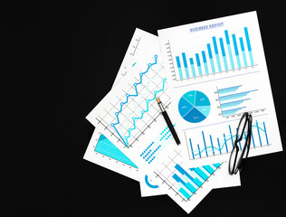 Financial graphs with pen and eyeglasses on the black background. Top view. Copy space.