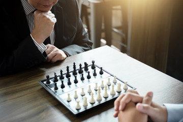 Confident businessman colleagues playing chess game overcome the fear of confrontation to development analysis new strategy plan, leader and teamwork concept for success