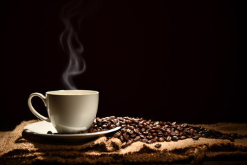 Cup of coffee with smoke and coffee beans on black background