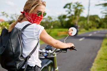 Beautful young biker female wears bandana and sunglasses, rides on fast motorbike, carries bag, waits for her companion, travels on bike. Spirit of freedom and independence. Outdoor actvities