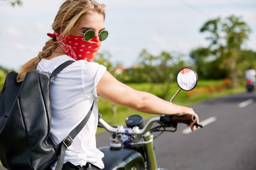 Pretty young hipster girl covers face with red bandana, has fast drive on motorbike, carries luggage, enjoys good road and fresh air. Fashion female model has journey alone on speed transport