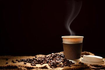 Paper cup of coffee with smoke and coffee beans on black background