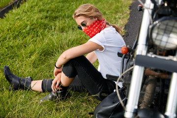 Outdoor lifestyle concept. Skilled female biker feels freedom as sits on green grass near her motorcycle, prepares for sport competitions, enjoys calm atmosphere in countryside.