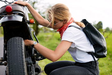 Female motorbiker repairs her bike, carries rucksack, has some problems with vehicle, tries to neutralize defect, stops on road. Woman does motorcycle maintenance outdoor. Motorist has troubles on way