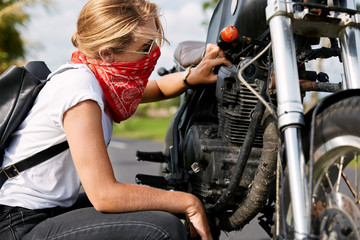 Professional young female biker in casual clothing, wears bandana covedred face, tries to solve mechanical problem with motorbike, stops on countryside road, repairs vehicle. Taking care of bike