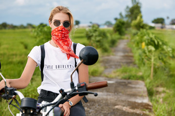 Horizontal shot of pleasant looking female model in sunglasses, drives on motorcycle in open air, admires fresh air and beautiful nature, has active lifestyle. Outdoor journey and feeling of freedom